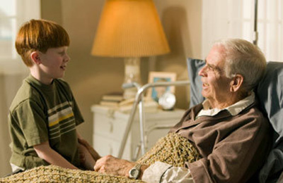 Young boy visits bed-ridden grandfather