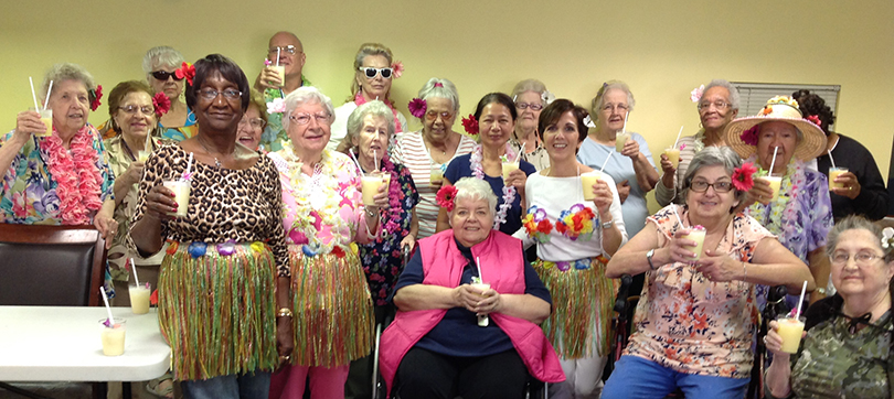Laurie Peters and senior housing residents celebrate Hawaiian style