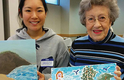 Co-ed and older woman display their paintings