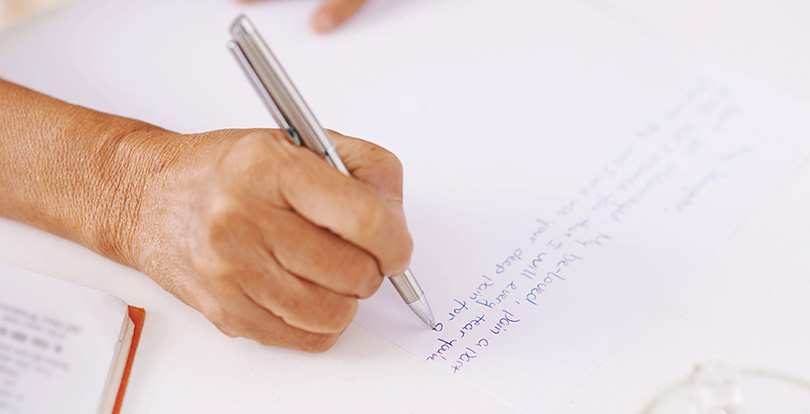 A hand with a pen writing
