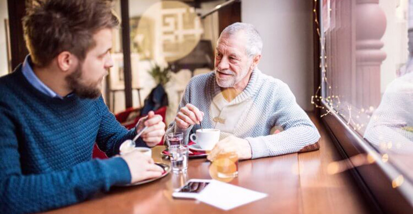 older and younger man enjoying coffee together