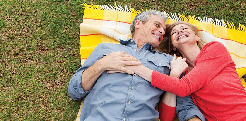 Couple laying on blanket on the grass