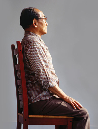 Man with great posture sitting in a chair.