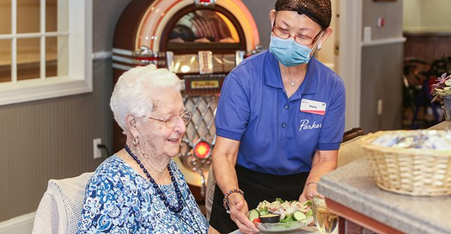 Elder woman served food by dining employee